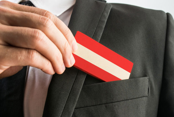 A man picks up a business card that looks like the flag of Austria