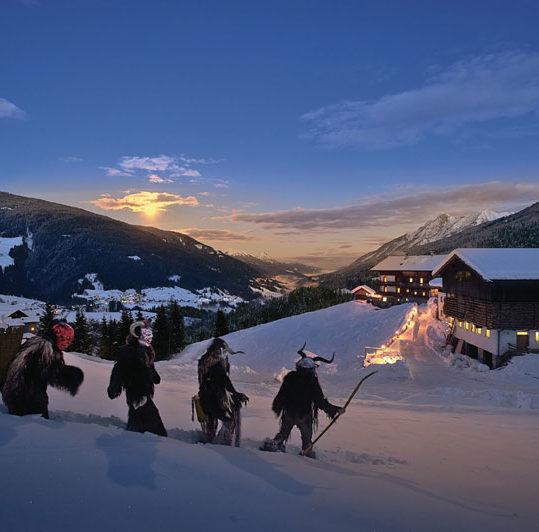 Krampus walking through the snow in Lechtal, Carinthia, Austria at night.
